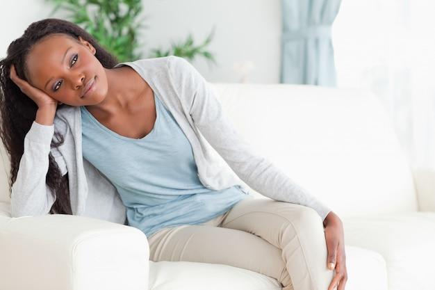 Chiuda in su della donna sul sofà nei pensieri