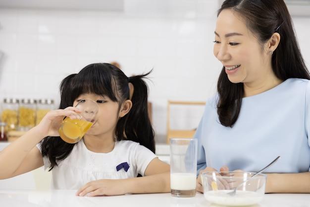 Chiuda in su della famiglia asiatica che beve il succo di arancia