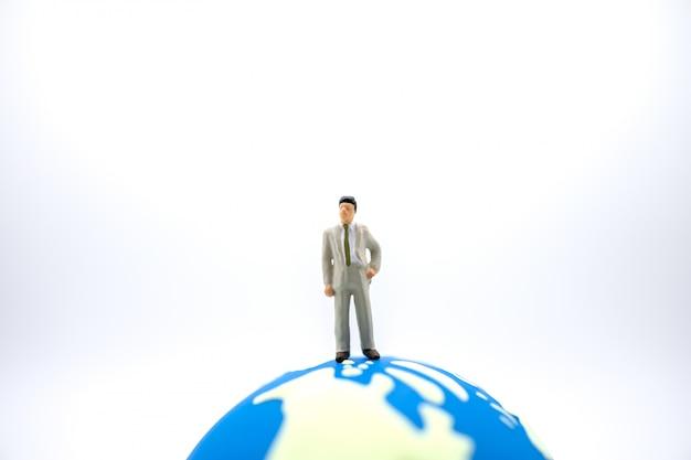 Chiuda in su della figura miniatura dell'uomo d'affari che si leva in piedi sulla mini sfera del mondo su bianco