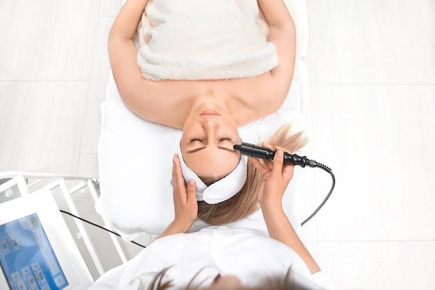 Chiuda in su della fine della donna in su che riceve il massaggio elettrico degli occhi facciali
