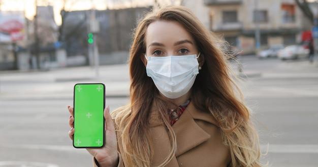 Chiuda in su della giovane donna caucasica nella mascherina medica che mostra il telefono verticale con lo schermo verde. ragazza con protezione antivirus che dimostra smartphone con il chroma key verticalmente in città.