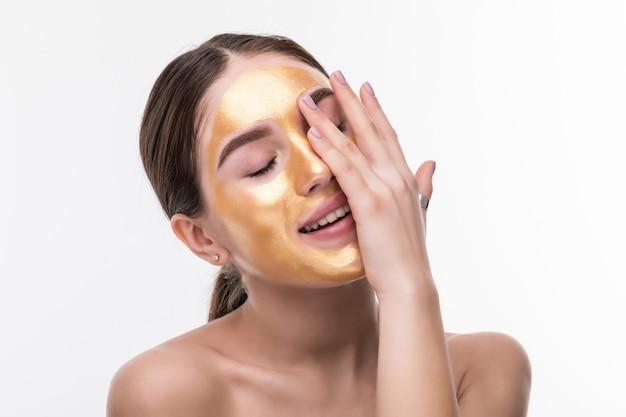 Chiuda in su della giovane donna in buona salute con la maschera di protezione cosmetica dell'oro su pelle molle.