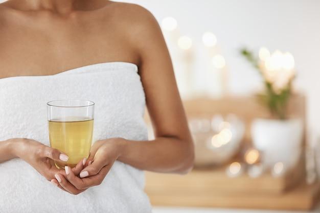 Chiuda in su della giovane donna in tovagliolo che giudica di vetro con tè verde nel salone della stazione termale.