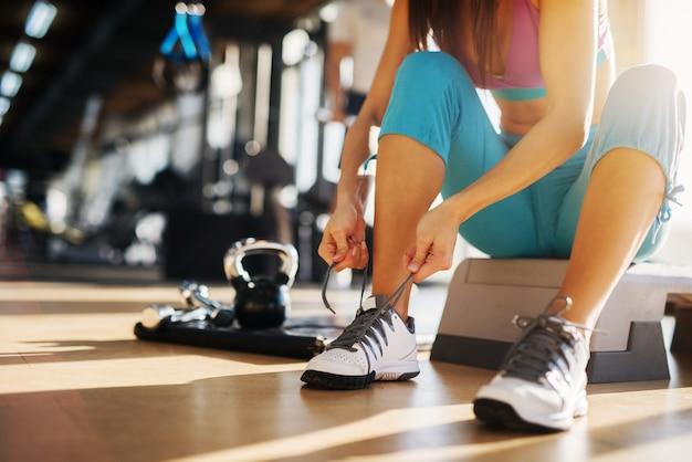 Chiuda in su della giovane ragazza sottile fitness seduto sullo stepper e legare i lacci delle scarpe in palestra.