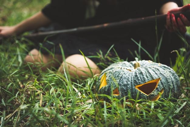 Chiuda in su della lanterna verde della zucca su erba con lo stregone femminile che tiene il personale magico