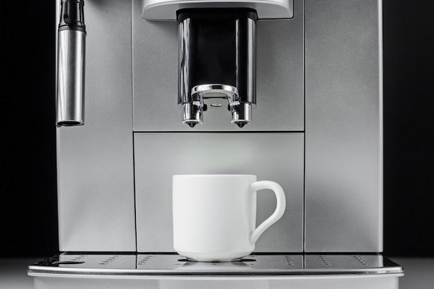 Chiuda in su della macchina per il caffè moderna e della tazza bianca