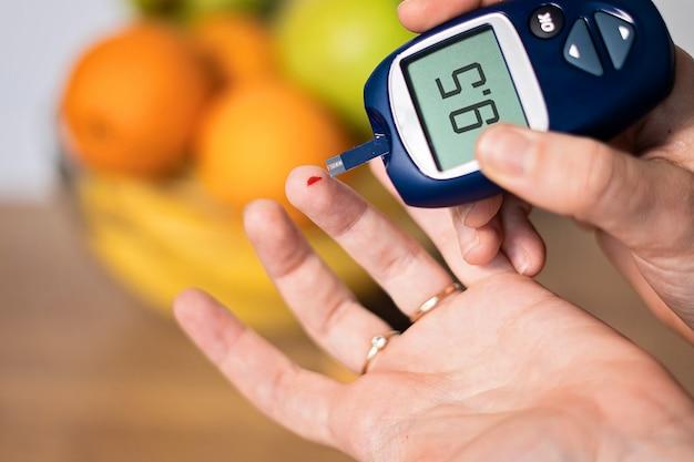 Chiuda in su della mano che misura il glucosio nel sangue a casa