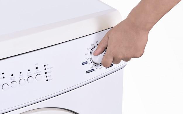 Chiuda in su della mano che registra il programma della lavatrice