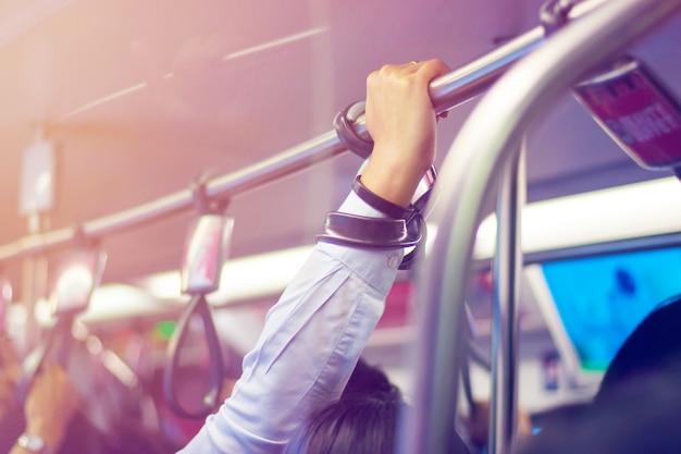 Chiuda in su della mano che tiene una maniglia sul treno elettrico