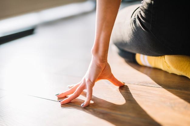 Chiuda in su della mano del ballerino sul pavimento