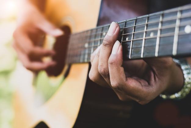 Chiuda in su della mano del chitarrista che gioca la chitarra. concetto musicale e strumento