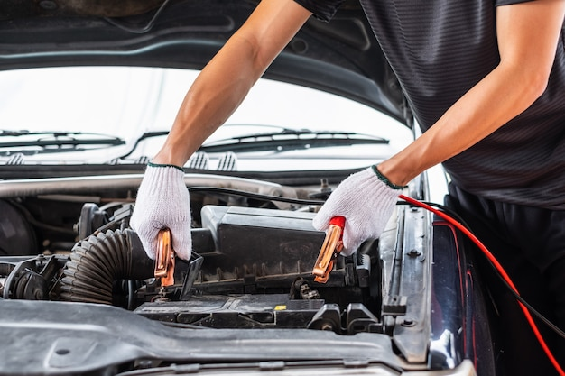 Chiuda in su della mano dell'uomo che carica una batteria dell'automobile