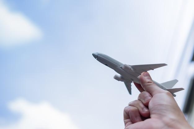 Chiuda in su della mano dell'uomo che tiene il giocattolo dell'aeroplano e alza fino al cielo