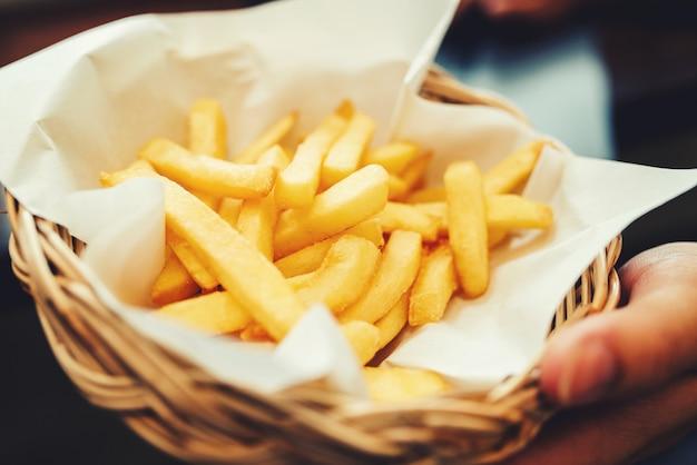 Chiuda in su della mano dell'uomo che tiene patatine fritte