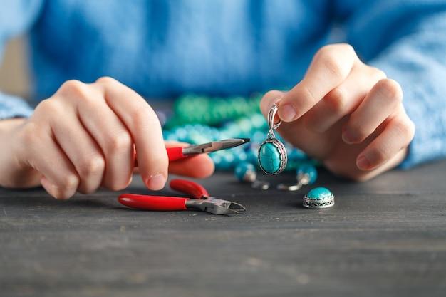 Chiuda in su della mano della donna che infila i branelli sulla coulisse per fare il braccialetto o la collana di perline artistica