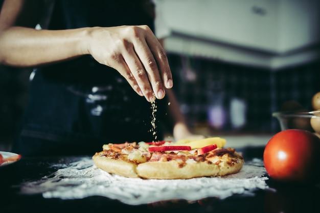 Chiuda in su della mano della donna che mette origano sopra il pomodoro e la mozzarella su una pizza.