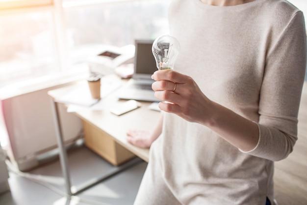 Chiuda in su della mano della donna che tiene una lampadina