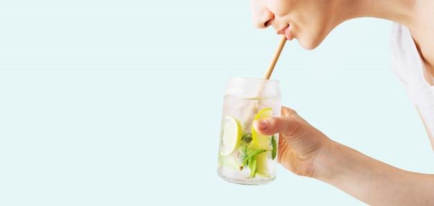 Chiuda in su della mano di una donna che tiene un bicchiere di cocktail mojito tropicale e sorseggiando attraverso una cannuccia