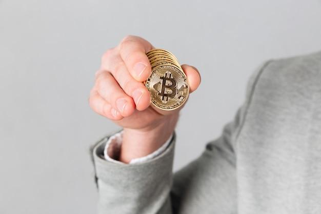 Chiuda in su della mano maschio che mostra il bitcoin dorato