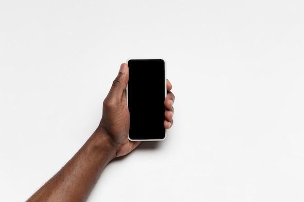 Chiuda in su della mano umana facendo uso dell'aggeggio con lo schermo nero in bianco