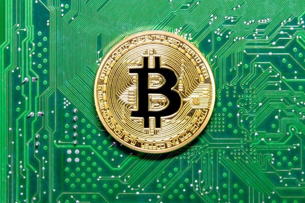 Chiuda in su della moneta dorata sul circuito stampato verde.