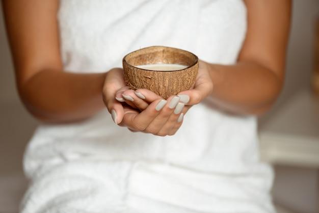 Chiuda in su della noce di cocco della holding della donna nel salone della stazione termale.