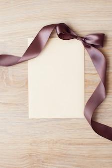 Chiuda in su della nota in bianco della scheda con il nastro marrone