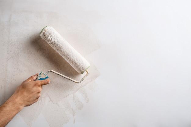 Chiuda in su della parete della pittura della mano con il rullo.