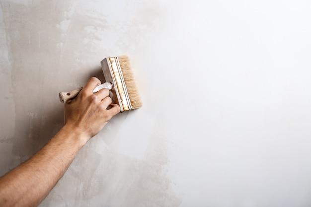 Chiuda in su della parete della pittura della mano con la spazzola.