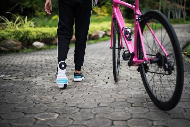 Chiuda in su della parte posteriore della donna con la bici della strada nel parco. concetto di salute e sport