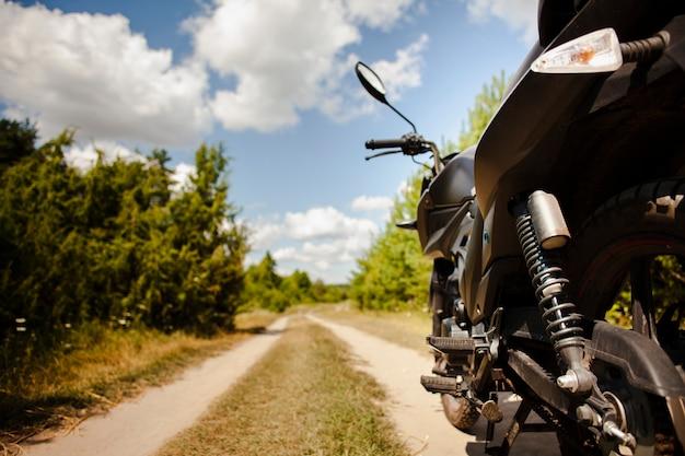 Chiuda in su della parte posteriore della motocicletta sulla strada non asfaltata