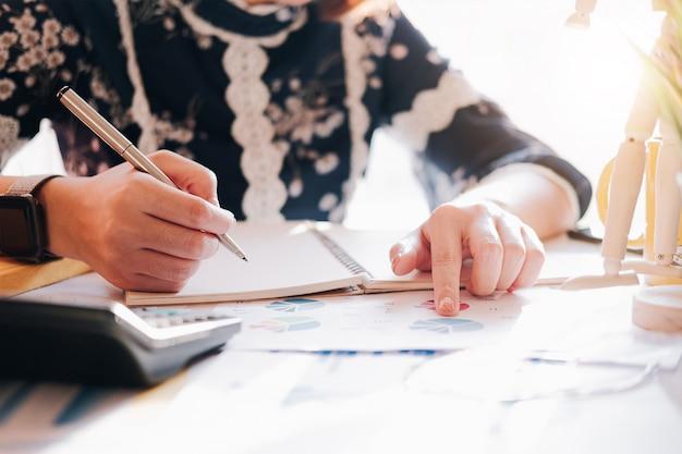 Chiuda in su della penna di tenuta della mano del ragioniere o della donna che lavora al computer portatile per il calcolo dei dati di affari, del documento contabile e del calcolatore all'ufficio, concetto di affari