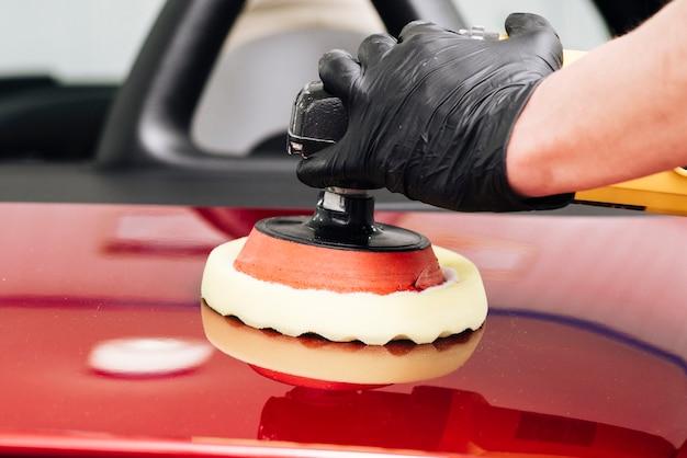 Chiuda in su della persona che pulisce l'esterno dell'automobile