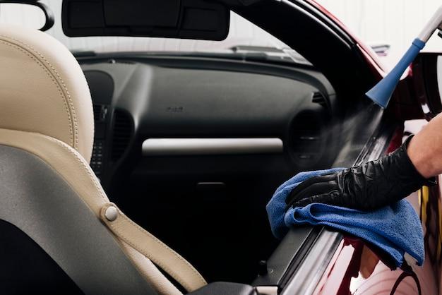 Chiuda in su della persona che pulisce l'interno dell'automobile
