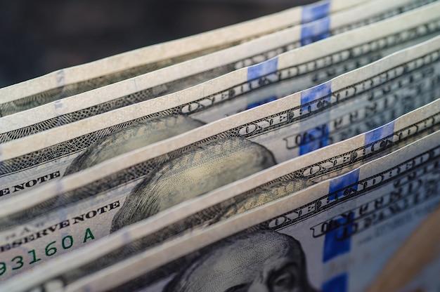 Chiuda in su della pila cento banconote in dollari