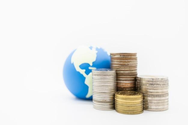 Chiuda in su della pila di monete davanti a mini palla del mondo