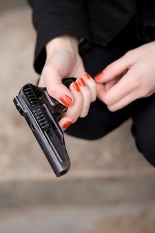 Chiuda in su della pistola in mani femminili