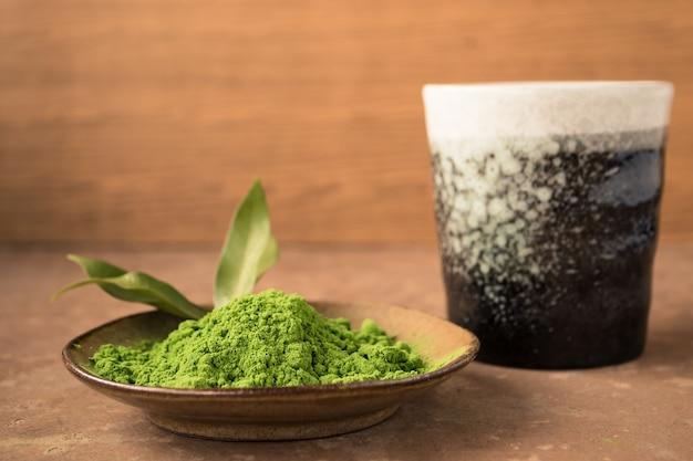 Chiuda in su della polvere del tè verde in piatto con la tazza di ceramica sulla tabella.