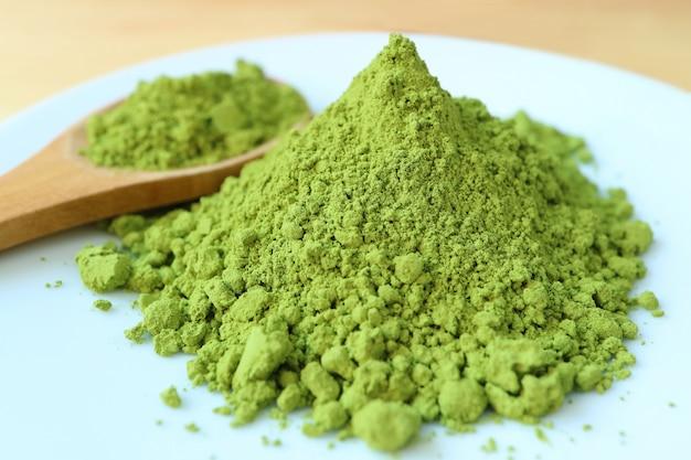 Chiuda in su della polvere vibrante del tè di matcha di colore verde, l'ingrediente per la fabbricazione del tè verde caldo