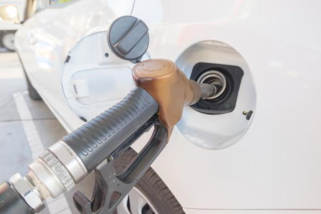 Chiuda in su della pompa a mano per aggiungere combustibile all'automobile bianca nella stazione di servizio