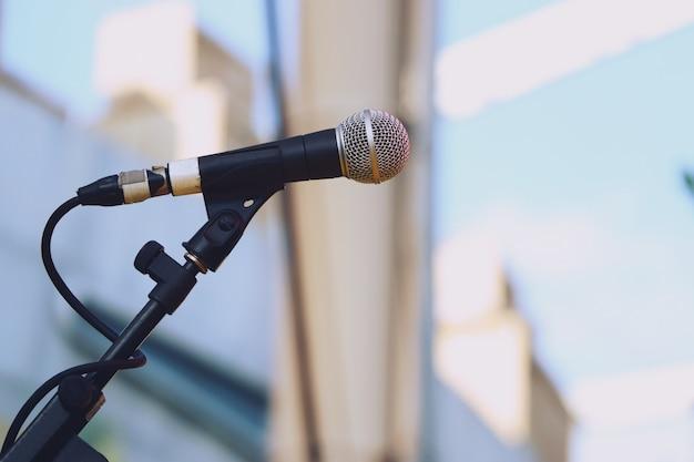 Chiuda in su della priorità bassa di luce del giorno del microfono in scena