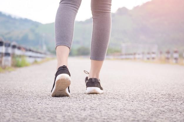 Chiuda in su della ragazza di forma fisica che cammina sulla strada