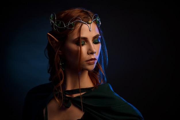 Chiuda in su della ragazza splendida in mantello verde smeraldo che nasconde i suoi occhi.