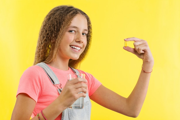 Chiuda in su della ragazza teenager che cattura la pillola con olio di fegato di merluzzo omega-3
