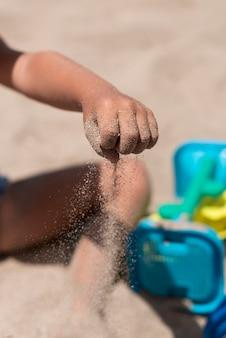 Chiuda in su della sabbia di versamento del bambino