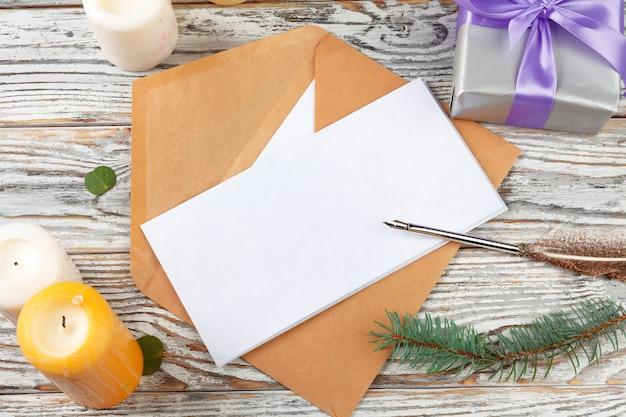 Chiuda in su della scrittura della lettera di natale sul documento giallo su priorità bassa di legno con le decorazioni