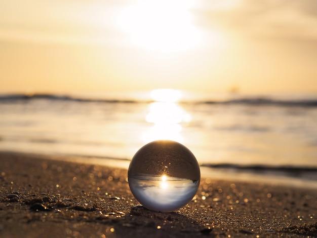 Chiuda in su della sfera con la riflessione dorata dell'alba alla spiaggia dell'estate