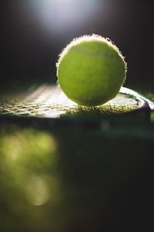 Chiuda in su della sfera di tennis con la racchetta