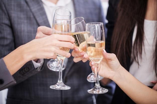 Chiuda in su della squadra di affari che tosta con champagne