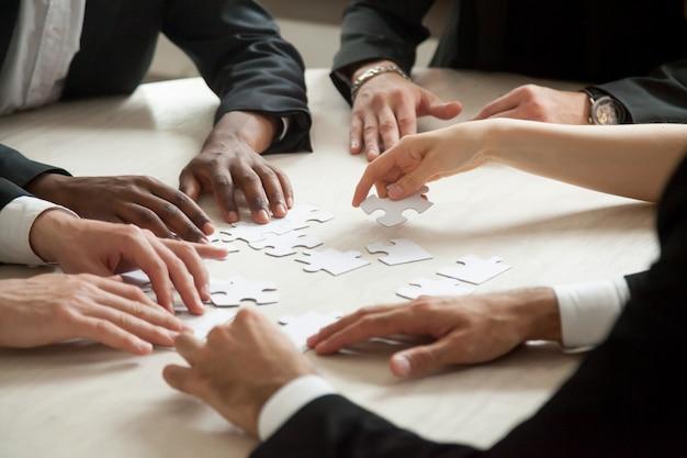 Chiuda in su della squadra multietnica che risolve il gioco in bianco di puzzle.